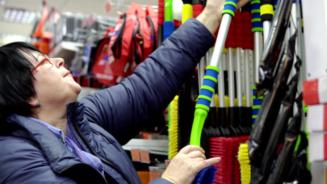 A-mature-woman-chooses-a-brush-with-scraper-in-the-supermarket-
