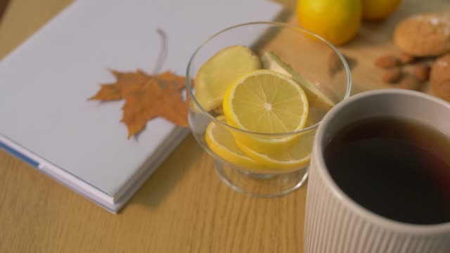 book-lemon-cup-of-tea-nuts-and-cookies-on-table