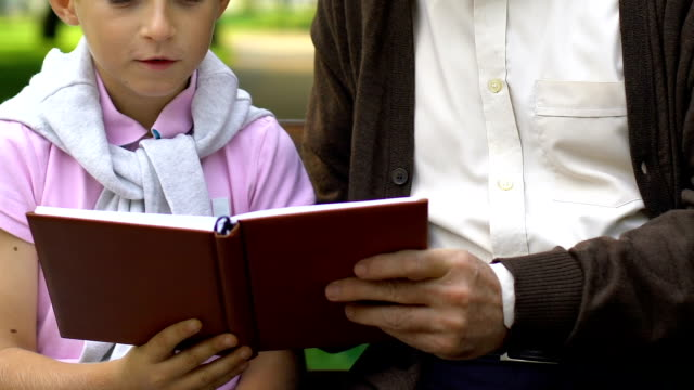 Grandfather-teaching-grandson-reading-resting-on-bench-in-summer-park-family
