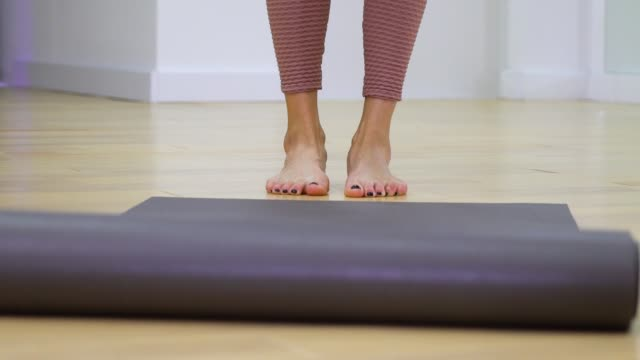 young-woman-feet-unrolling-mat-and-stepping-on-it-in-slow-motion