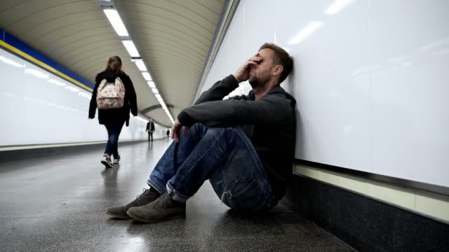 Sad-jobless-young-man-crying-suffering-depression-stress-sitting-on-ground-street-subway-tunnel-looking-desperate-leaning-on-wall-alone-in-Mental-disorder-Emotional-pain-Drug-abuse-and-Alcoholism-