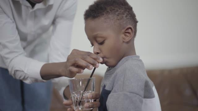 Madre-cariñosa-ayudando-al-pequeño-niño-afroamericano-a-beber-agua