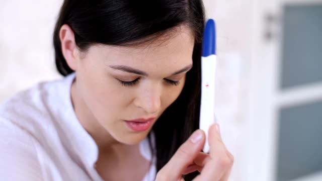 Mujer-triste-con-prueba-de-embarazo-en-casa