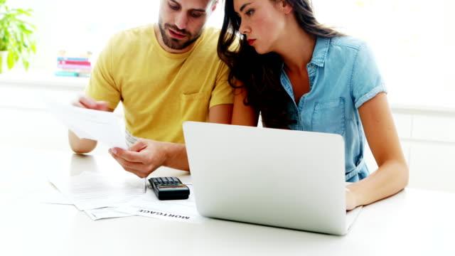 Preocupados-par-calcular-sus-facturas-con-el-ordenador-portátil-en-la-cocina