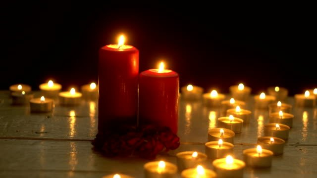 Candles-burning-lights-on-white-wood-table