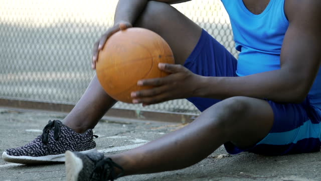 Male-warming-up-with-basket-ball-waiting-for-team-players-outdoor-activities