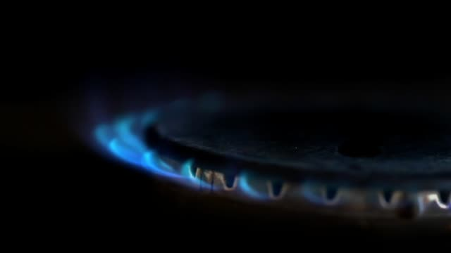 Close-up-of-gas-stove-blue-flame-lit-in-a-dark-kitchen