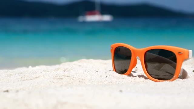 Bright-orange-Fashion-sunglasses-on-the-white-sand-of-a-tropical-beach