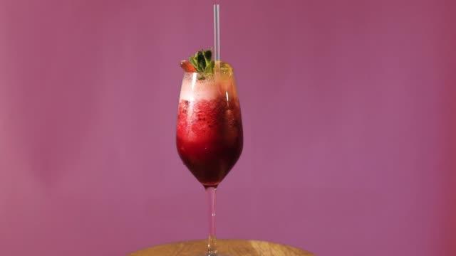 Der-Cocktail-dreht-sich-auf-einem-farbigen-Hintergrund-der-Cocktail-dreht-sich-um-die-eigene-Achse-der-Cocktail-mit-Eis-verziert-mit-Minze