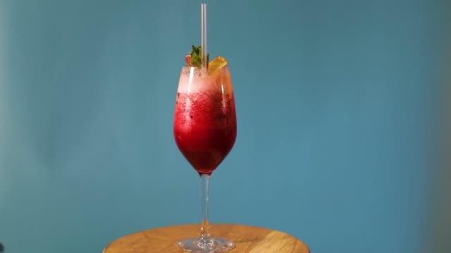 Rot-auf-blauem-Hintergrund-cocktail-cocktail-dreht-auf-blauem-Hintergrund-alkoholischen-Cocktail-auf-blauem-Hintergrund