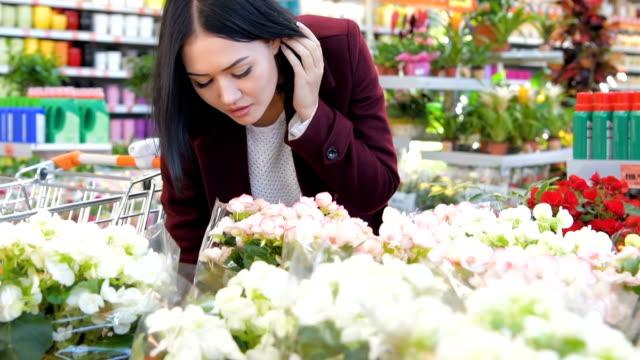 Mujer-que-huele-a-flores-en-invernadero-en-cámara-lenta