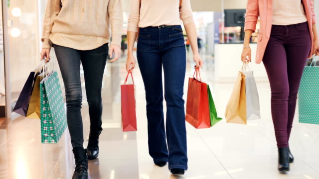 Low-shot-of-ladies-legs-walking-in-shopping-center-with-paper-bags-enjoying-buying-clothes-and-presents-Youth-lifestyle-friendship-and-consumerism-concept-