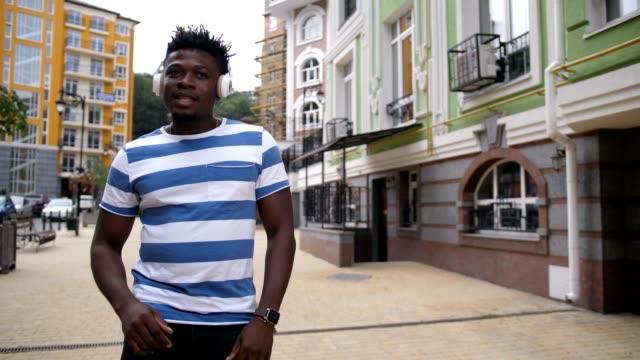 Cheerful-guy-enjoying-afrohouse-music-on-street