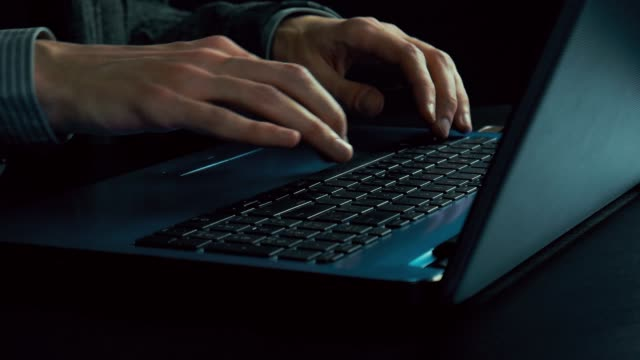 Man-s-hands-typing-text-on-a-laptop-Late-evening-Dark-office-Slow-motion