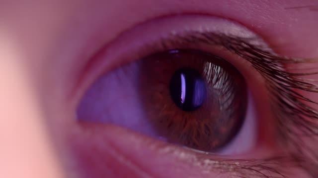 Toma-de-cerca-de-l-ojo-mirando-hacia-la-derecha-con-reflejo-de-la-lámpara-violeta-en-él-