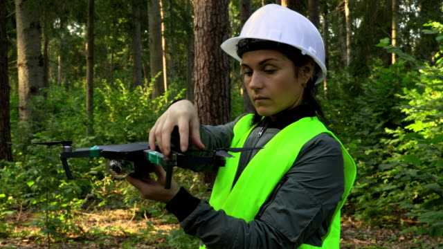 Woman-Worker-prepares-Drone-Quadcopter-for-video-forest-inspection