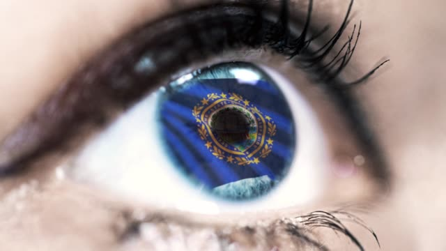 Woman-blue-eye-in-close-up-with-the-flag-of-New-Hampshire-state-in-iris-united-states-of-america-with-wind-motion-video-concept