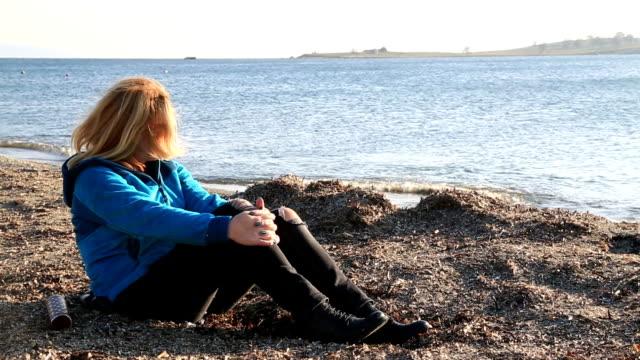 Mujer-triste-sentada-en-la-orilla-del-mar