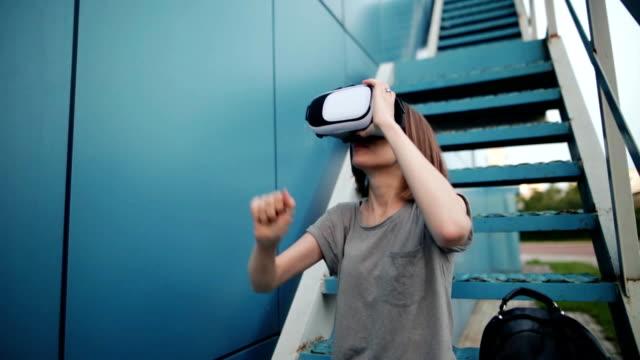 Futuro-es-ahora-Hermosa-mujer-joven-en-una-juego-de-gafas-vr-las-escaleras-Mujer-joven-caucásica-toque-algo-utilizando-gafas-de-realidad-virtual-moderna-sobre-un-fondo-azul-