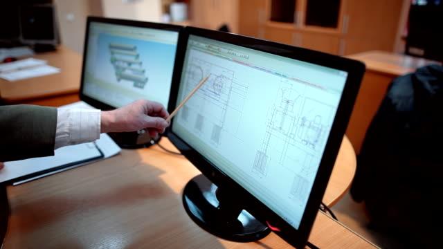 En-la-oficina-de-ingenieros-revisión-y-discuten-los-detalles-en-los-esquemas