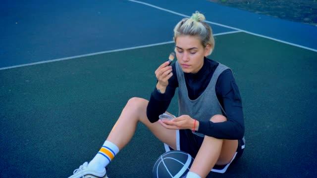 Schöne-junge-blonde-weibliche-Basketballspieler-Make-up-zu-tun-und-sitzen-auf-dem-Boden-mit-Ball,-Sportkleidung-tragen