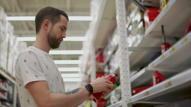 Driver-man-is-holding-a-pneumatic-lift-jack-in-hand-in-a-shop-for-automobilists
