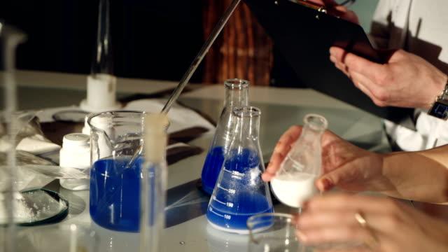 Scientists-examining-liquids-in-beakers-