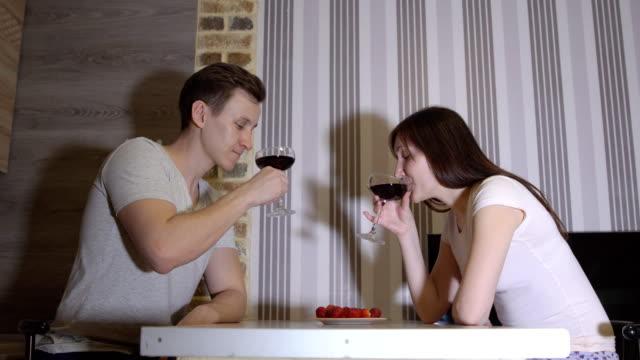 Noche-romántica-Joven-pareja-en-una-mesa-bebiendo-vino
