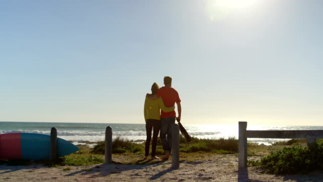 Rear-view-young-couple-standing-on-the-beach-4k