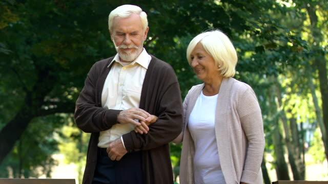 Mayor-pareja-abrazarse-y-caminar-en-el-parque-de-verano-disfrutando-juntos-de-pasatiempo