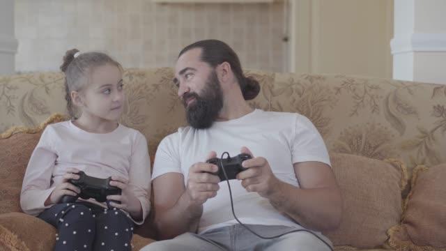 Kleine-Tochter-mit-ihrem-lustigen-Vater-die-Videospiele-im-Fernsehen-mit-großen-Emotionen-im-gemütlichen-Wohnzimmer-spielt-