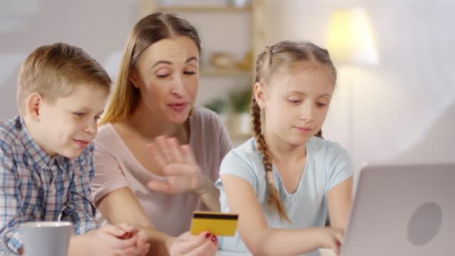 Mutter-und-Kinder-kaufen-online-mit-Computer