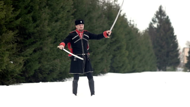 Un-joven-con-ropa-cosaca-balanceando-una-espada-en-un-paisaje-invernal-en-la-nieve-