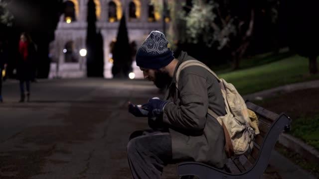 Mendigo-solitario-caminando-en-la-calle-en-noches-de-Roma-fondo