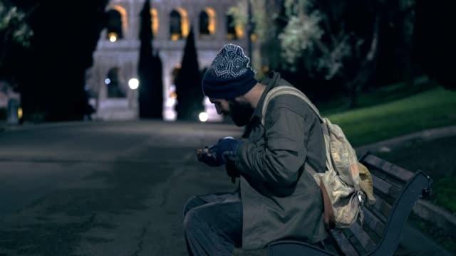 hombre-sin-hogar-sentado-en-un-banco-cuenta-con-dinero-en-la-noche