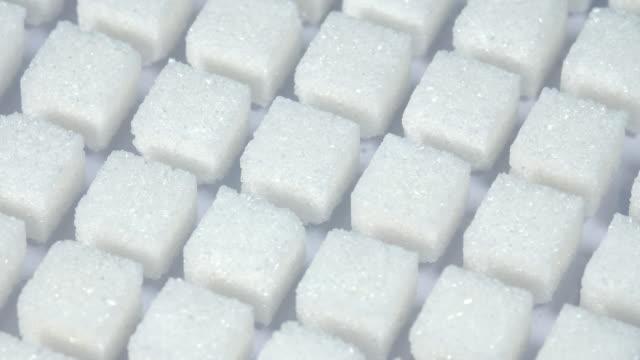 Mesa-Tiro-cubitos-de-grupo-de-azúcar-varían-de-posición-en-fondo-azul-claro