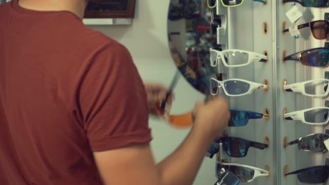Un-joven-caucásico-es-cerca-de-un-deportivo-de-pasamano-gafas-para-deportes-ciclismo-y-recoge-gafas-en-una-tienda