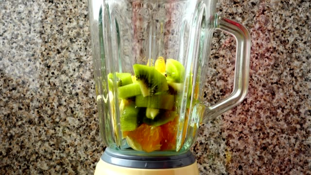 Filling-in-the-blender-of-a-kiwi-oranges-and-bananas-Preparation-of-smoothie-in-the-blender-