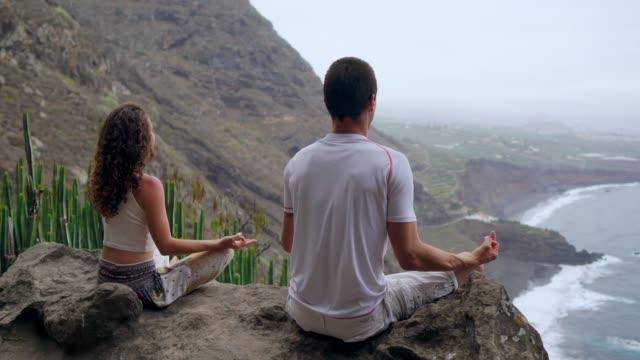 Ein-Mann-und-eine-Frau-sitzen-auf-einem-Berg-der-Blick-auf-den-Ozean-sitzt-auf-einem-Stein-in-einem-Lotussitz-meditieren-Die-Ansicht-von-hinten-Kanarische-Inseln