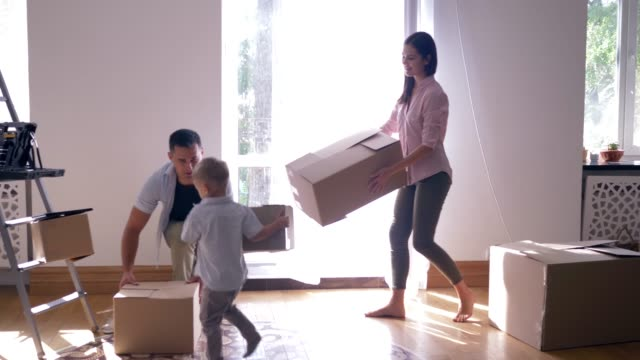 relocation-to-new-flat-happy-family-with-small-child-boy-enjoys-new-home-after-repair-among-boxes-with-things