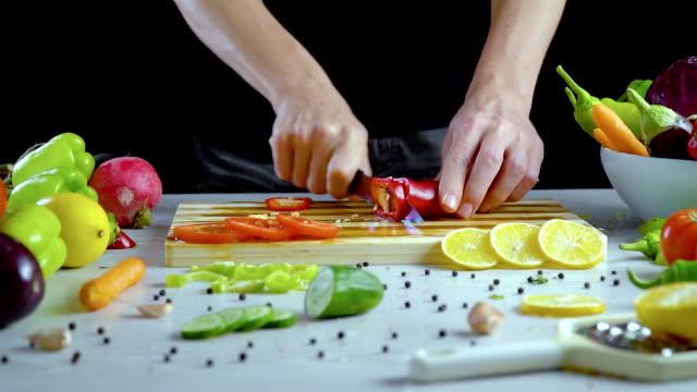 El-hombre-es-vegetales-de-corte-en-la-cocina-cortar-el-pimiento-rojo