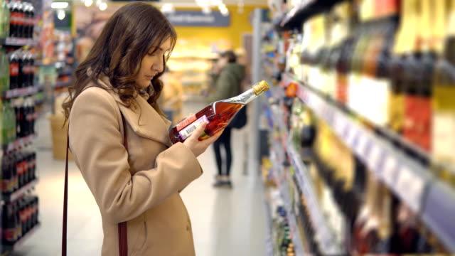 Hermosa-mujer-elige-vino-rosado-en-un-departamento-de-supermercado