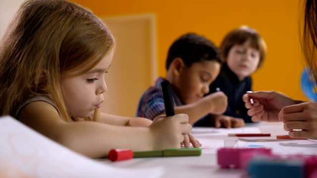 Cute-engrossed-little-girl-drawing-at-art-lesson