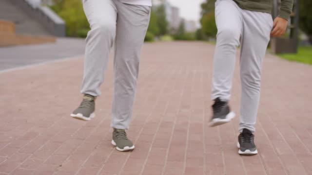 Beine-von-Mutter-und-Sohn-tun-Knie-Rotation-Übung-im-Freien