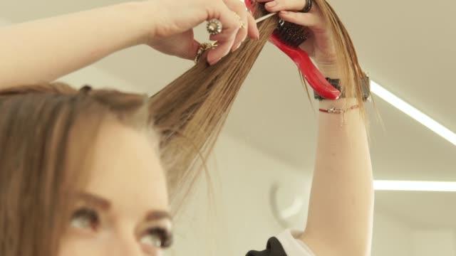 Peluquero-cortar-el-cabello-largo-con-las-tijeras-profesionales-de-peluquería-Cerca-de-haircutter-haciendo-corte-de-pelo-de-mujer-con-unas-tijeras-en-el-salón-de-belleza