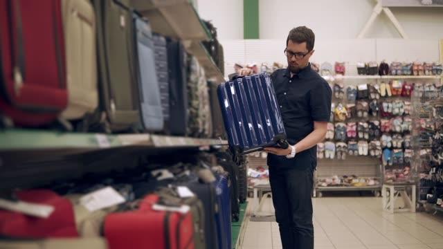 Shopper-hombre-es-tomando-maleta-plástico-del-estante-de-un-supermercado-inspección