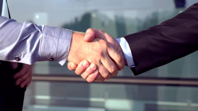 Der-erfolgreiche-Unternehmer-begrüßen-einander-nahe-Bürogebäude-hautnah-Zwei-junge-Kolleginnen-und-Kollegen-zu-treffen-und-Händeschütteln-im-urbanen-Umfeld-Handschlag-von-Geschäftspartnern-im-Freien-Seitenansicht