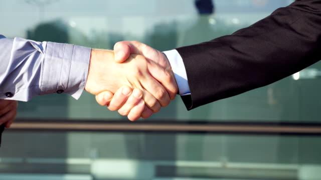 Dos-empresarios-confío-en-estrechar-las-manos-después-de-éxito-cerca-de-edificio-de-oficinas-Jóvenes-colegas-felicitando-mutuamente-en-medio-urbano-Apretón-de-manos-de-los-socios-comerciales-Cámara-lenta