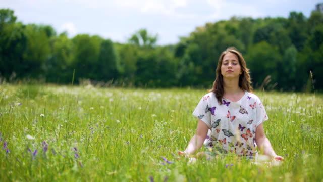 Frau-sitzt-in-Lotus-Pose-meditieren-im-Freien-Wind-bewegt-sich-Haare-Einssein-Natur