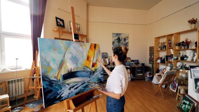 Schwenken-Sie-Schuss-der-Malerin-Darstellung-Meereslandschaft-auf-Leinwand-mit-Ölfarben-Pinsel-und-Palette-in-Werkstatt-allein-Visuelle-Kunst-und-Jugend-Konzept-